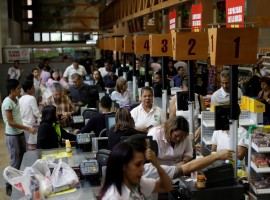 People buy food and other staple goods inside a supermarket in Caracas. Venezuela is undergoing a major economic crisis, with many suffering from food shortages and runaway inflation.