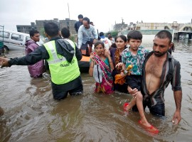 Fire officials and rescuers evacuate people from a flooded neighbourhood after heavy rains in Ahmedabad.