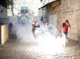 Palestinians react as a stun grenade explodes in a street at Jerusalem's Old city outside the compound known to Muslims as Noble Sanctuary and to Jews as Temple Mount, after Israel removed all security measures it had installed at the compound July 27, 2017.
