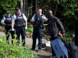 A family claiming to be from Haiti is confronted by Royal Canadian Mounted Police (RCMP) officers as they cross the US-Canada border. More than 4,300 asylum seekers crossed the U.S. border into Canada in the first six months of this year. Many told Reuters they feared Trump's immigration crackdown.