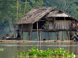 Villagers take shelter in a partially submerged house following floods at Baghmari village in Nagaon district, in the northeastern state of Assam, India.
