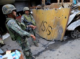 Government soldiers stand on guard in front of damaged buildings as troops continue their assault on its 105th day of clearing operations against pro-IS militants who have seized control of large parts of Marawi City, Philippines September 4, 2017.