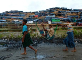 Rohingya refugee children carry an old woman in a sling near Balukhali makeshift refugee camp in Cox's Bazar, Bangladesh.