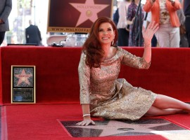 Actor Debra Messing poses on her star after it was unveiled on the Hollywood Walk of Fame in Los Angeles.