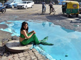 Sonu Gowda poses as a mermaid in front of a pothole where artist Baadal Nanjundaswamy created an art work on Cubbon Road.