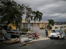 Alfredo Martinez, a mail man for the U.S. Postal Service delivers the mail at an area damaged by Hurricane Maria in San Juan. Only 15 percent of electrical power has been restored since the storm bludgeoned the U.S. territory on Sept. 20, but 99 of Puerto Rico's 128 post offices are delivering mail. Tents have taken the place of post offices wrecked by Maria.