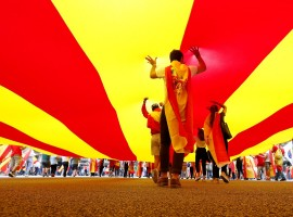 People walk under a huge Catalan flag during Spain's National Day in Barcelona.
