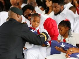 La David Johnson Jr. son of U.S. Army Sergeant La David Johnson, is presented with an American flag.