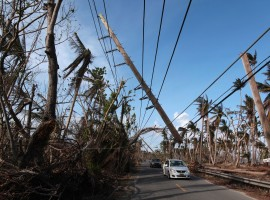 Cars drive under a partially collapsed utility pole in Naguabo.