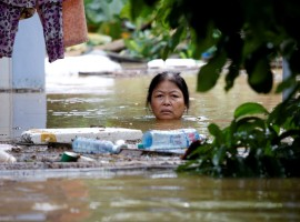 A woman wades through a submerged street in the UNESCO heritage town of Hoi An. The death toll from a typhoon and ensuing floods in Vietnam reached 61 on Monday and the government said some reservoirs were dangerously near capacity after persistent rain.