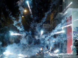 A firework explodes next to a riot policeman during clashes following a rally marking the 44th anniversary of a 1973 student uprising against the military dictatorship that was ruling Greece, in Athens, Greece.