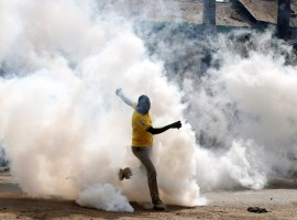 A man makes his way through rising tear gas fired by riot police officers to disperse supporters of Kenyan opposition leader Raila Odinga in Nairobi.