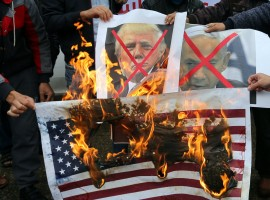 Palestinians burn posters depicting Israeli Prime Minister Benjamin Netanyahu and President Donald Trump during a protest against the U.S. intention to move its embassy to Jerusalem and recognize the city as the capital of Israel, in Rafah in the southern Gaza Strip.