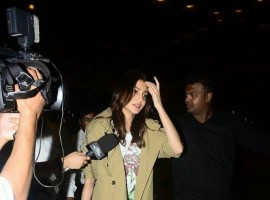 Bollywood Actress Anushka Sharma and her family members were dogged by questions on rumours about her wedding to star cricketer Virat Kohli as they made their way into the airport here to take off reportedly for Italy.