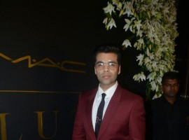 Karan Johar poses for photographers on her arrival at Mickey Contractor's MAC party in Mumbai.