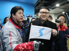 A man impersonating Kim Jong Un holds a Korean unification flag.