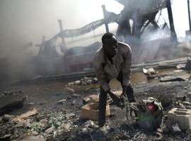 A man looks for goods amid the rubble outside of the Marche Hyppolite (Hyppolite Market), also known as Marche en Fer (Iron Market), after a fire that affected part of the market and the surrounding stands in Port-au-Prince, Haiti.