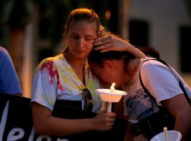 Tori Stetzer (L) and Taylor Miler, both of Parkland, react during a candlelight vigil fas they hold placards with the names of victims of the shooting in Parkland, Florida at Florida Atlantic University in Boca Raton, Florida, February 16, 2018.