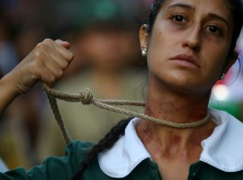 A woman shows a noose around her neck as she takes part in a rally in Santiago, Chile.