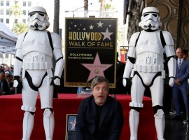 Mark Hamill poses on his star with Stormtroopers.