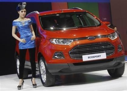 A model poses beside a Ford Ecosport during a media presentation of the 34th Bangkok International Motor Show in Bangkok March 26, 2013.