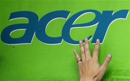 A man's hand is seen on an Acer logo as he pastes a poster below at a computer mart in Taipei