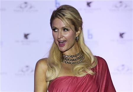 Paris Hilton poses for photographers while wearing an Indian-inspired dress during a news conference in Mumbai