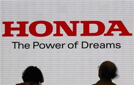 Visitors are silhouetted against a Logo of the Honda Motor at the company showroom in Tokyo