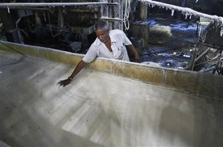 A worker spreads sugar inside a sugar factory at Sanyan village in Gujarat April 23, 2012.