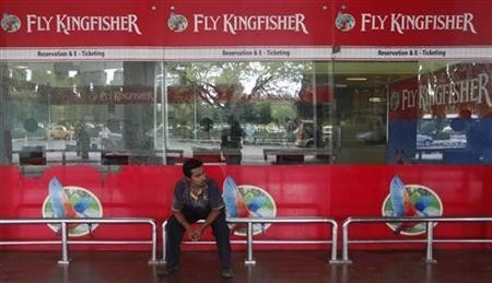 An airlines staff member sits in front of a closed Kingfisher Airlines ticketing counter at the airport in Kolkata October 3, 2012.