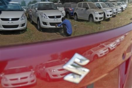 A worker cleans a Maruti Suzuki Swift Dzire car at the company's stock yard at Sanand in Gujarat.