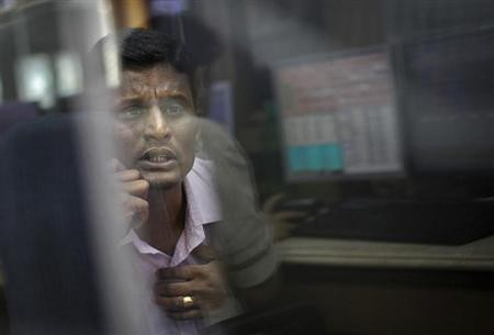 A broker looks at a computer screen as he talks on a phone at a stock brokerage firm in Mumbai December 3, 2012.