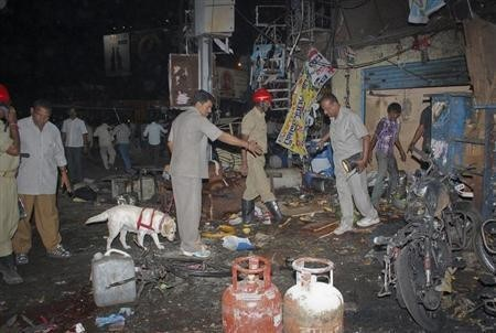Investigating officers use a sniffer dog as they inspect the site of an explosion at Dilsukh Nagar, in Hyderabad February 21, 2013.