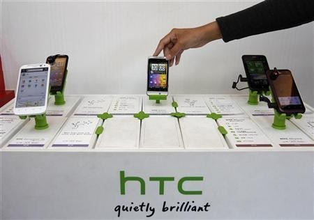 A shop attendant arranges HTC phones in a mobile phone store in Taipei November 24, 2011.