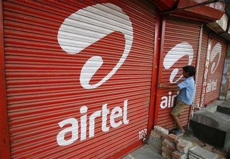A boy closes the shutter of a shop painted with an advertisement for Bharti Airtel in the western Indian city of Ahmedabad.