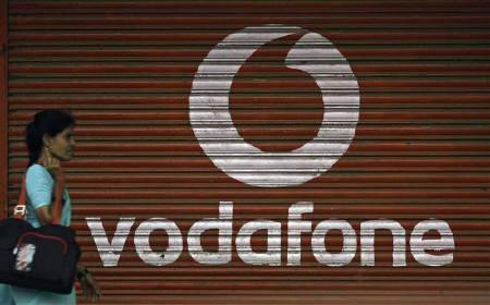 A woman walks past a large logo of Vodafone displayed on a shop in Mumbai May 20, 2010.