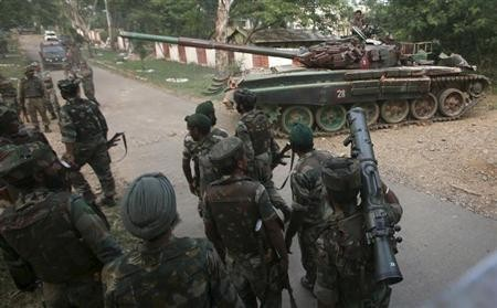 A tank from the Indian army moves past soldiers during a search operation after a gun battle at an army camp in Mesar in Samba district September 26, 2013.