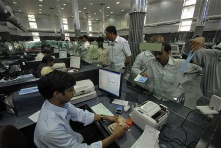A cashier (L) counts currency notes as customers wait inside a bank in Hyderabad March 22, 2010.
