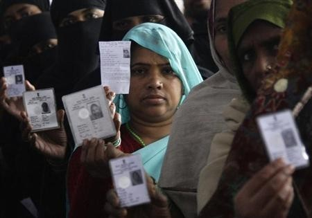 Voters display their voter identity cards as they wait for their turn to cast their ballot at a polling station in Uttar Pradesh. (Representational image)
