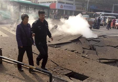 Policeman accompanies a woman after the oil pipeline exploded in China