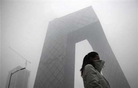 A woman walks past the new China Central Television (CCTV) building amid heavy fog in Beijing, December 5, 2011.