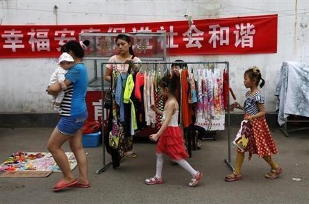 A family walk past a vendor selling women's clothes along a market street at a residential area for migrant workers in Beijing
