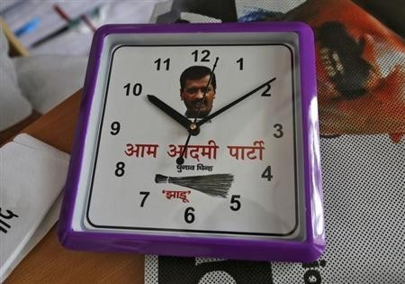 A wall clock carrying a portrait of Arvind Kejriwal, leader of the newly formed Aam Aadmi (Common Man) Party (AAP), and party symbol of a broom, lies on a table inside their party office in New Delhi October 1, 2013