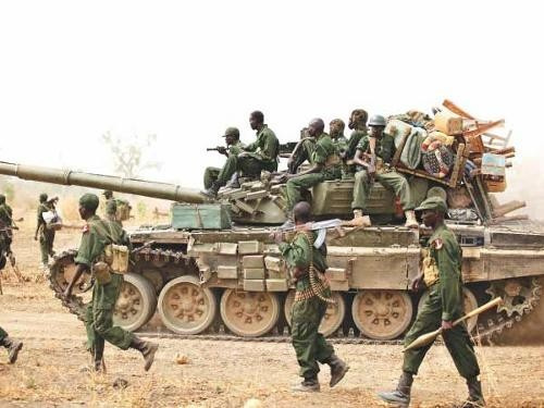 South Sudanese soldiers walk alongside a tank as they withdraw from the town of Jau, at the disputed border with Sudan .
