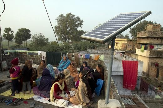 Local women of Dharnai sing on roof of a house where solar panels are installed