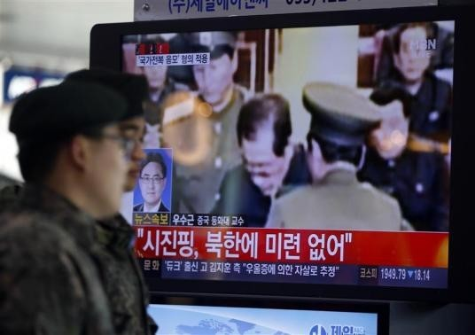 South Korean soldiers walk past a television showing reports on the execution of Jang Song Thaek, who is North Korean leader Kim Jong Un's uncle, at a railway station in Seoul December 13, 2013.