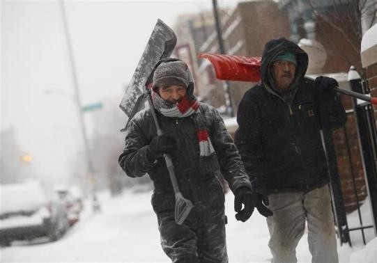 Two men carry shovels as they walk along through several inches of snow in Detroit, Michigan January 2, 2014