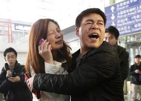 A Relative (Woman in White) of a Passenger Onboard Malaysia Airlines Flight MH370 Cries as She Talks on Her Mobile Phone at the Beijing Capital International Airport on 8 March, 2014