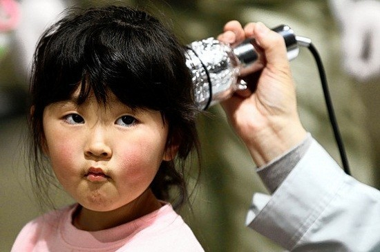 A young girl receives a radiation scan in Fukushima prefecture