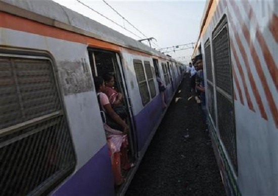 Passengers ride at the open doorways of commuter trains in Mumbai
